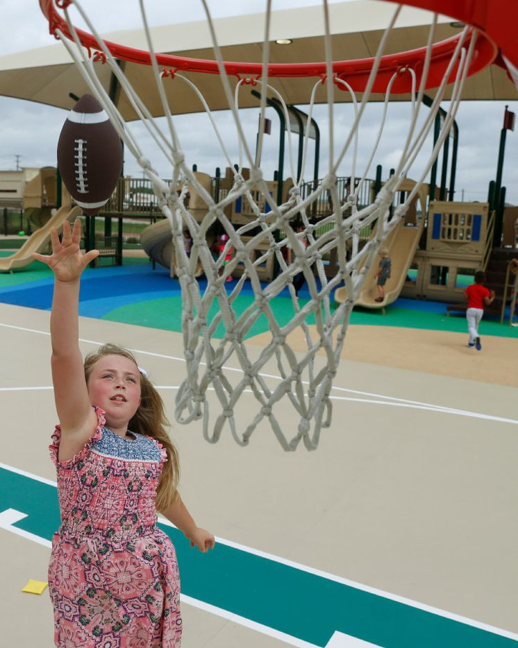 Adyson Jolley, 8, tosses a football into basketball net will playing on the Children's Learning Adventure Childcare Centers playground in McKinney on June 14.  The company is expanding with new campuses coming to Allen and Flower Mound.