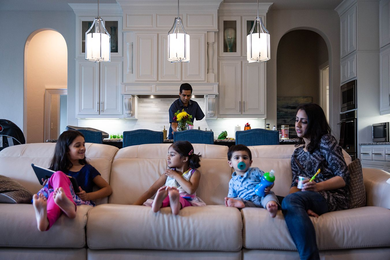 Naveed Khan cooks lunch for his wife, Ayesha, and children, Nazneen, 7, Yasmeen, 4, and Rehan, 1, in their home in Southlake.