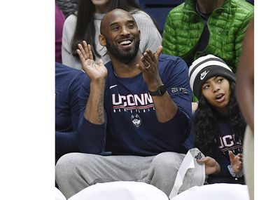 In this March 2, 2019 photo, Kobe Bryant and his daughter Gianna watch the first half of an NCAA college basketball game between Connecticut and Houston in Storrs, Conn. Dads with daughters inspired by Kobe Bryant's special bond with his 13-year-old Gianna took to social media to celebrate their own daughters in words and photos using the hashtag #GirlDads. Bryant and his daughter died in a helicopter crash on Sunday, Jan. 26, 2020.