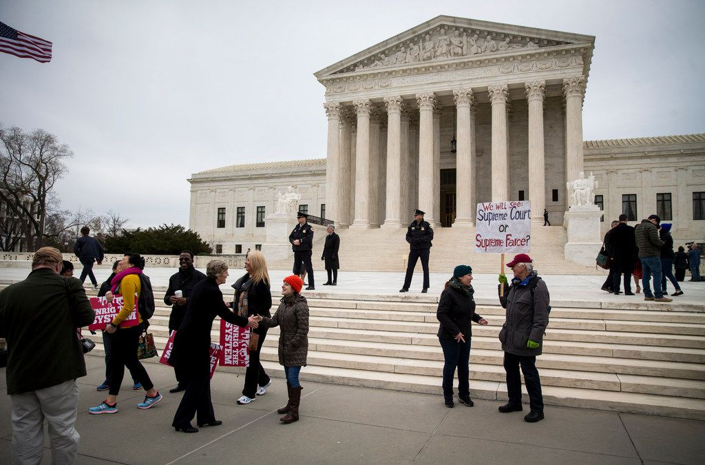 People gather outside of the Supreme Court in Washington, Feb. 26, 2018. The Supreme Court on Monday declined to clear the way for the Trump administration to end the Obama-era program that protects about 700,000 young immigrants from deportation, meaning that the so-called Dreamers could remain in legal limbo for many months unless Congress acts to make their status permanent.