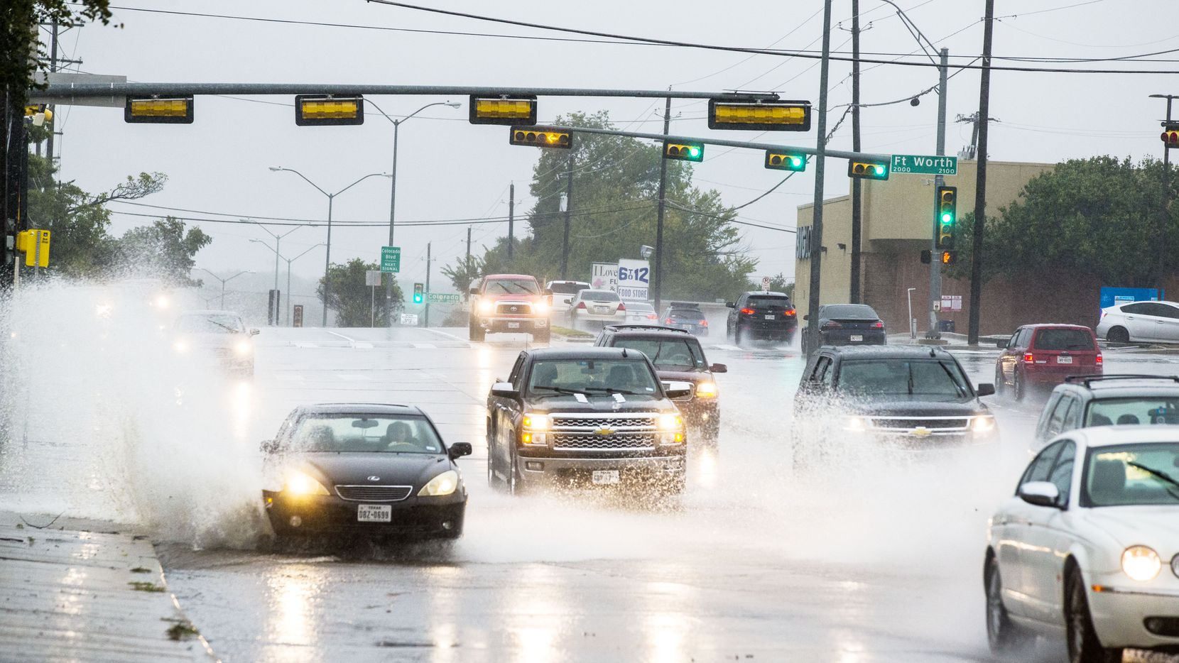 Cars drove through standing water on North Hampton Road in Dallas on Oct. 13.