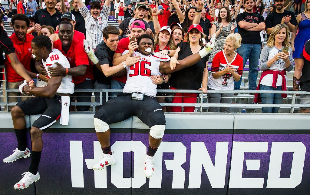 FILE - Texas Tech defensive lineman Broderick Washington (96) and wide receiver Michael Coley (80) celebrate with fans after a 27-24 victory over TCU in double-overtime of an NCAA football game at Amon G. Carter Stadium on Saturday, Oct. 29, 2016, in Fort Worth.