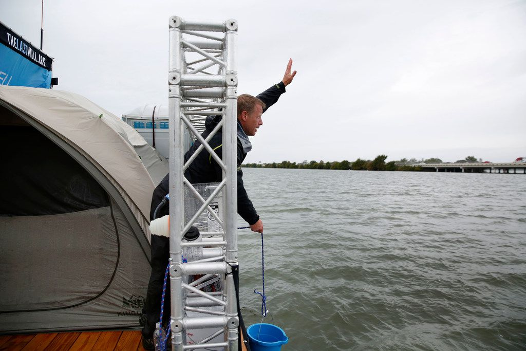 Todd Phillips, founder and director of the Last Well, waves to a driver who honked at him from Interstate 30 on his wooden barge on Lake Ray Hubbard in Rockwall, Texas, on Wednesday, Oct. 17, 2018. Phillips is planning to stay on the barge until he is able to raise $2 million for Liberians to have clean water.