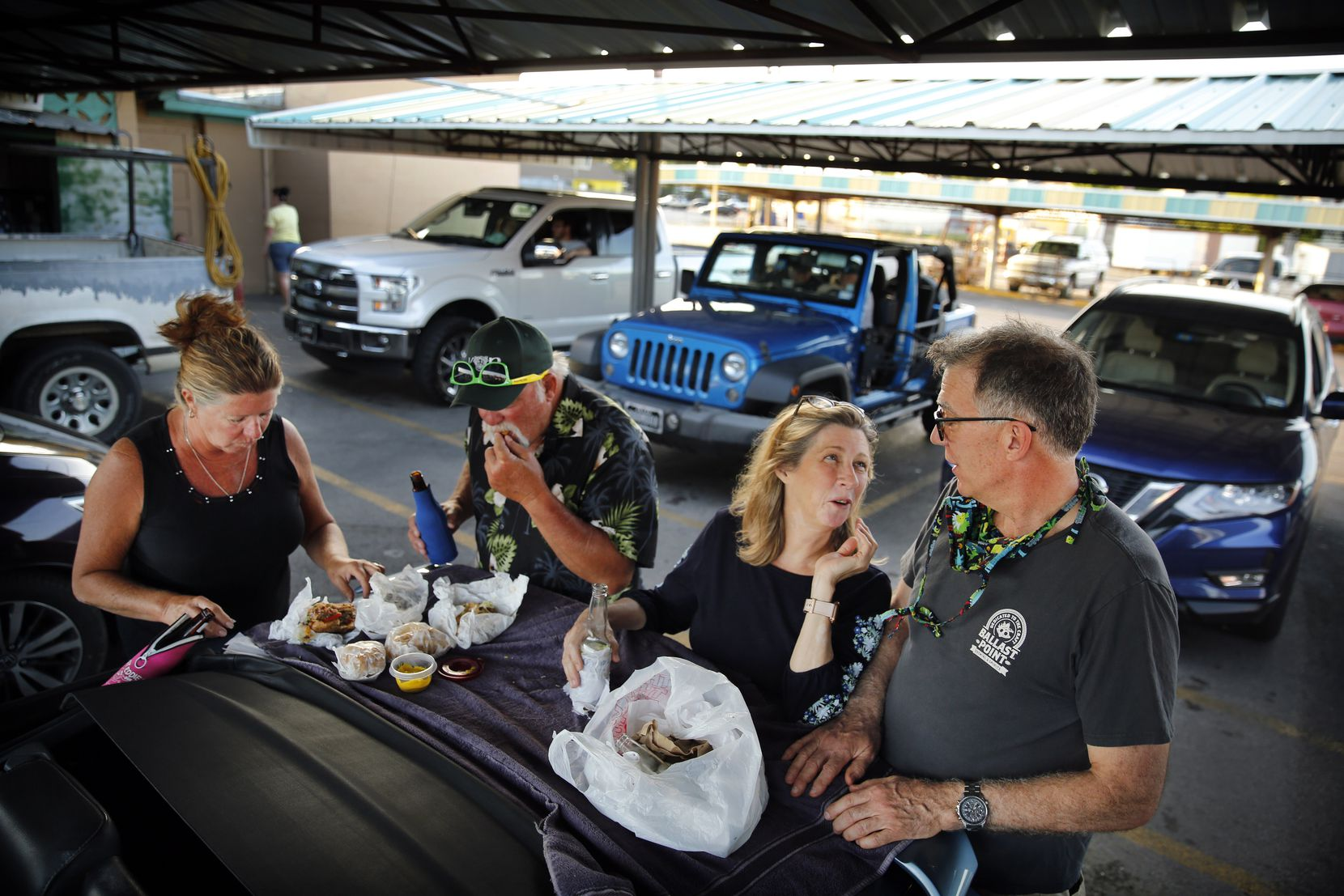 Dallas friends (from left), Donna and her husband Dennis Bardin, Laura Mallett and her sweetheart Randy Olena visit while having burgers and beers on the trunk of a Ford Mustang at Keller's Drive-In.