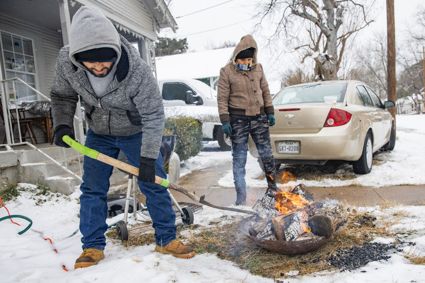 Leonel Solis (left) and Estefani Garcia get ready to cook outside of their home in East Dallas on Wednesday, Feb. 17, 2021. The couple, who lost power on Sunday, have been using electricity from a neighbor's generator and heat from their car to stay warm.