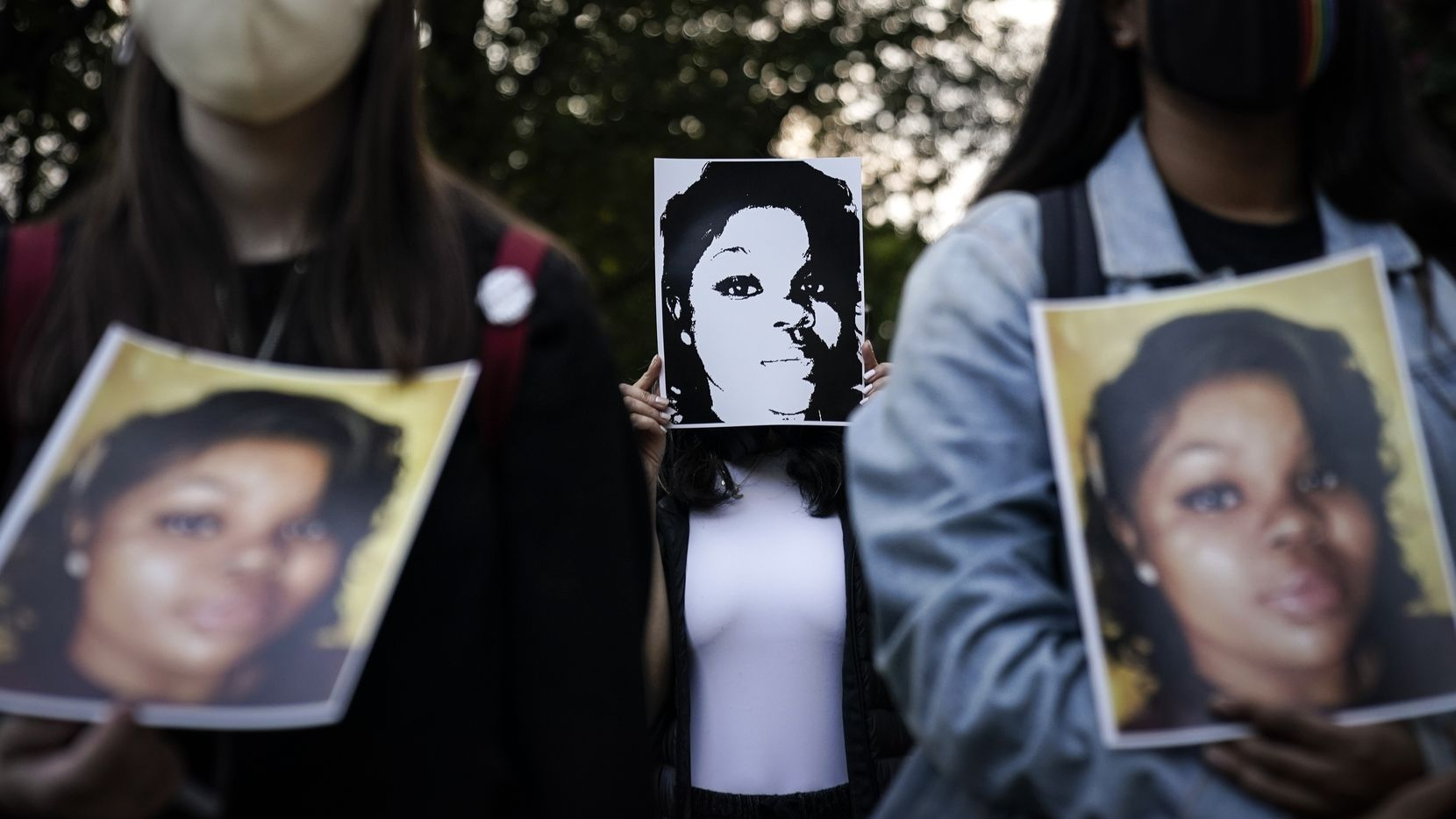 Demonstrators holding up images of Breonna Taylor rally in front of the U.S. Department of Justice building after grand jurors declined to indict Louisville, Ky., police officers on murder charges in Taylor's death in March.