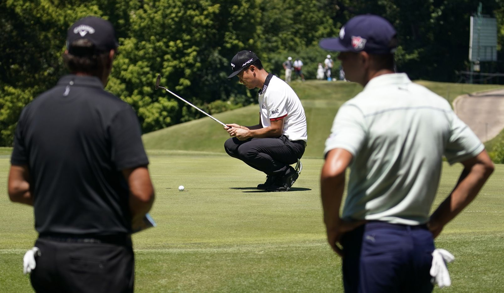 PGA Tour golfer Kevin Na lines up his putt on No. 8 as he plays with Phil Mickelson (left) and Gary Woodland  during the second round of the Charles Schwab Challenge at the Colonial Country Club in Fort Worth, Friday, June 12, 2020.  The Challenge is the first tour event since the COVID-19 pandemic began. (Tom Fox/The Dallas Morning News)