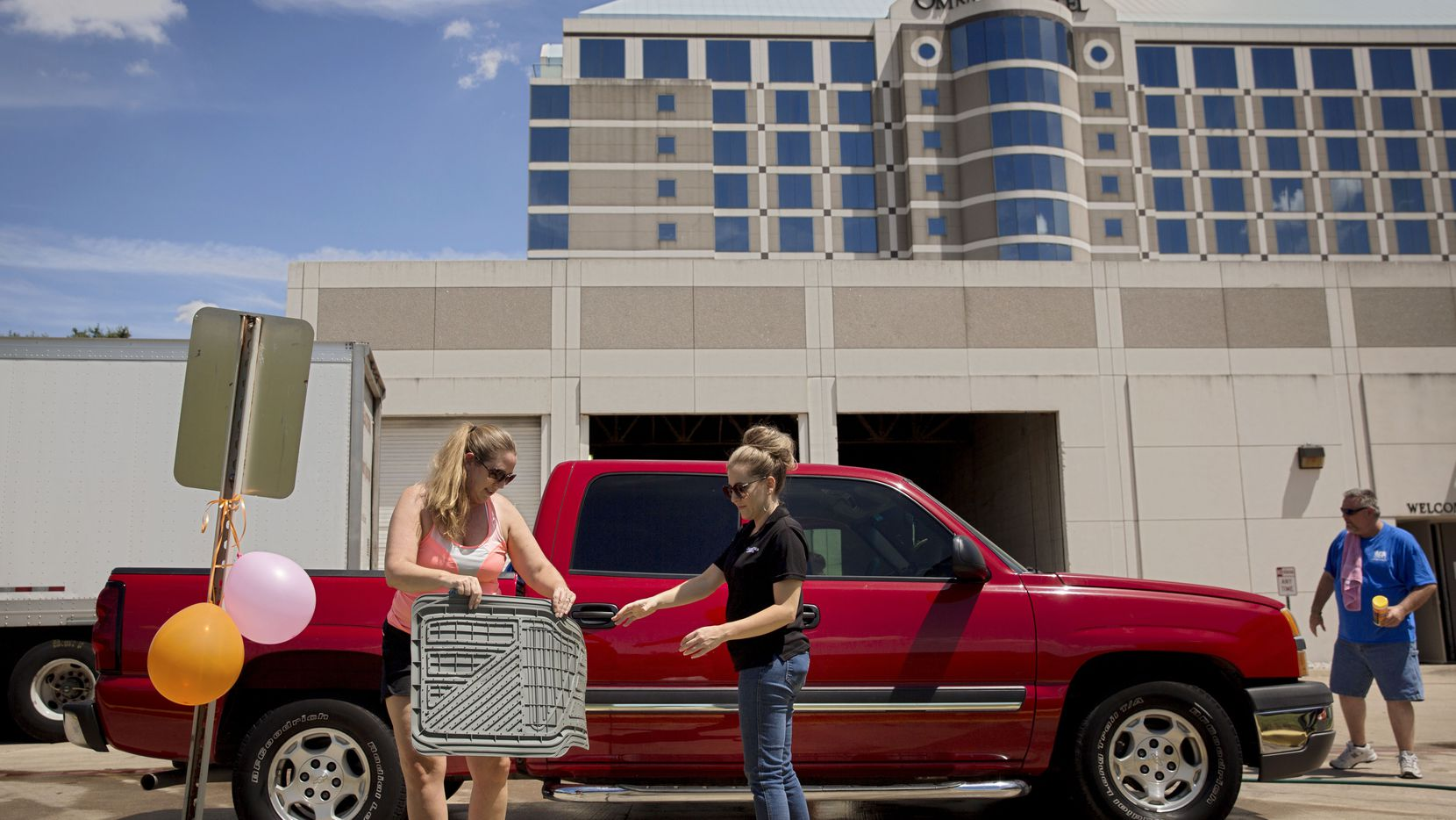 From left: Omni Dallas Park West Hotel employees Maggie Rich, Shayla Truesdell and David Carlile washed a coworker's truck in 2016 in Dallas. Employees at the hotel were raising money for the American Heart Foundation.