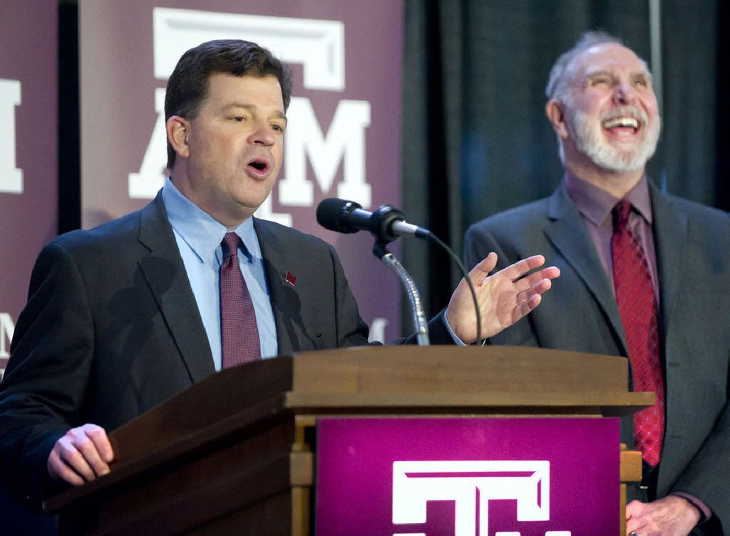 Texas A&M president Michael Young (right) laughs as new A&M athletic director Scott Woodward responds to a question on the possibility of A&M and Texas playing each other in football during an introductory press conference Monday in the Hall of Champions at Kyle Field. (Dave McDermand/The Eagle)