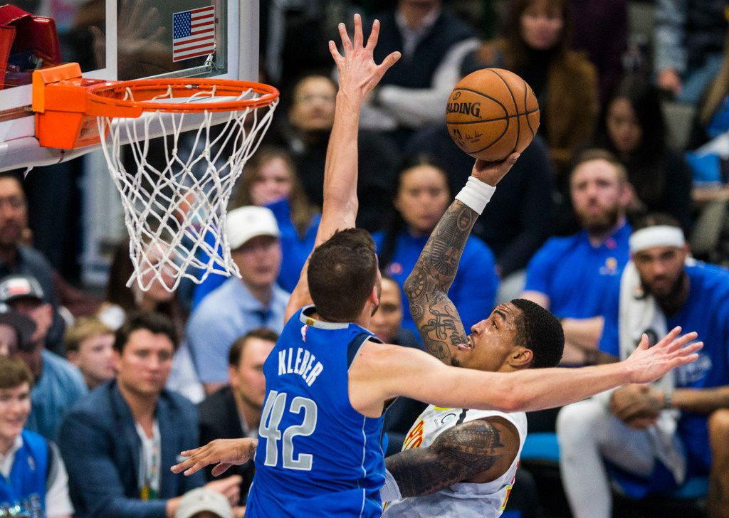 FILE - Mavericks forward Maxi Kleber (42) tries to block a shot by Hawks forward John Collins (20) during the third quarter of a game on Saturday, Feb. 1, 2020, at American Airlines Center in Dallas.