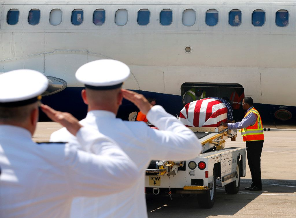 Navy officers salute as the remains of Navy Seaman 1st  Class (E3) George A. Coke Jr. of Arlington are unloaded from a commercial flight at Dallas-Fort Worth International Airport, Friday, June 23, 2017. Coke, who perished in the USS Oklahoma after it sank at Pearl Harbor, was identified through recent DNA testing. The North Texas Patriot Guard Riders joined the procession to Moore Funeral Home in Arlington. A service for Coke will be held at First United Methodist Church in central Arlington Saturday before being buried at Parkdale Cemetery.