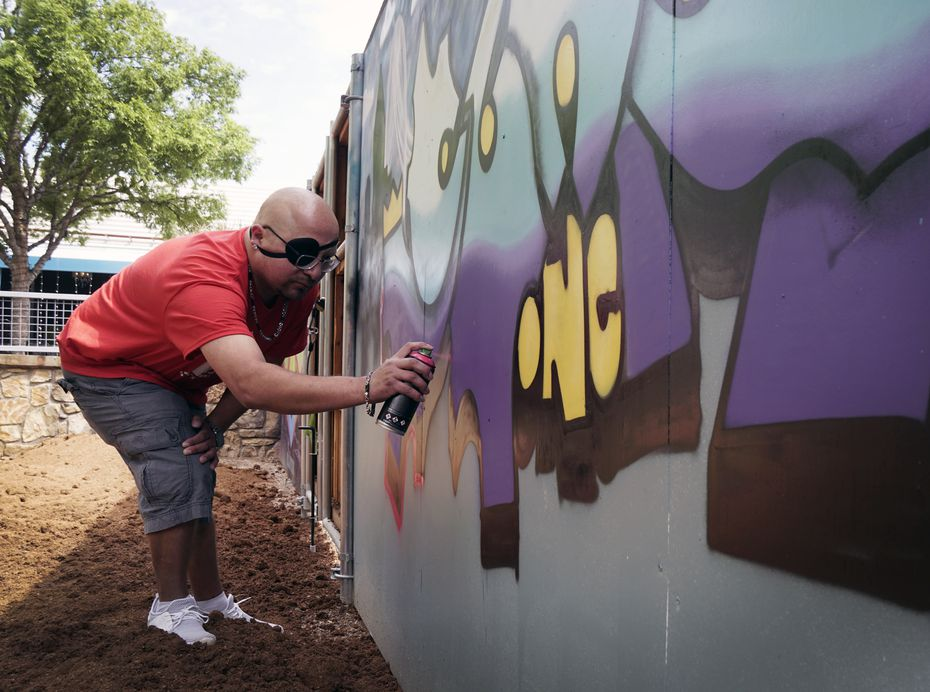 King Suner1 paints a mural on a wall in the Art Park and beer garden at Trinity Groves in West Dallas.