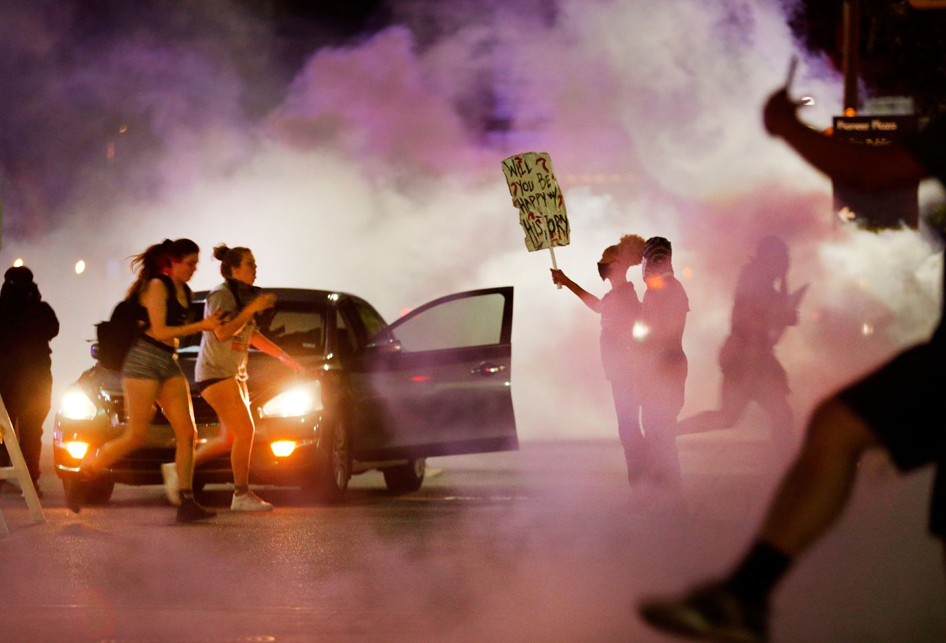 A woman holds a sign reading 'Will You Be Happy With History?' as protestors are overcome with tear gas run from Dallas Police tactical officers at Young St. and S. Griffin St. in downtown Dallas, Friday, May 29 2020. People were marching in protest of the in-custody death of George Floyd when they confronted Dallas Police tactical officers and tear gas was fired.
