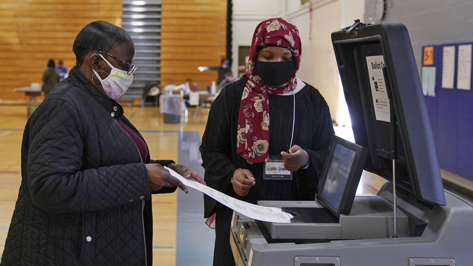 Election judge Naima Hussen watched as Elizabeth Boykin cast her ballot at North High School in Minneapolis on Tuesday.