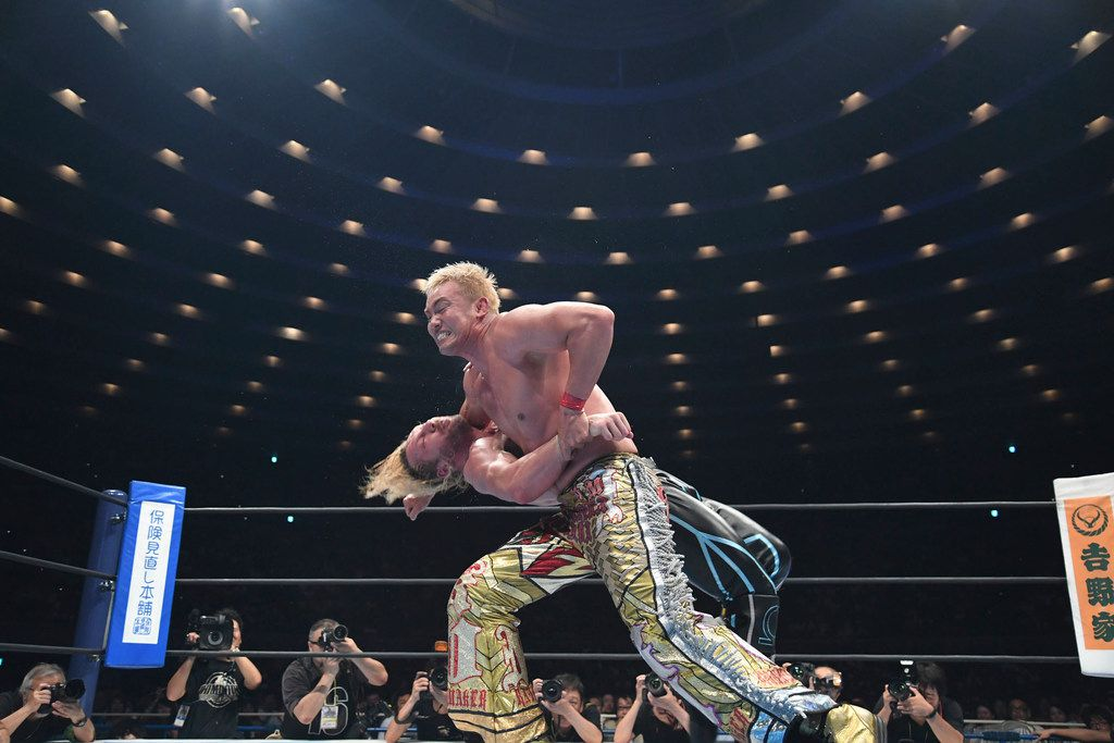 Professional wrestlers Kazuchika Okada (top, front) and Kenny Omega face off in Japan's version of WWE.