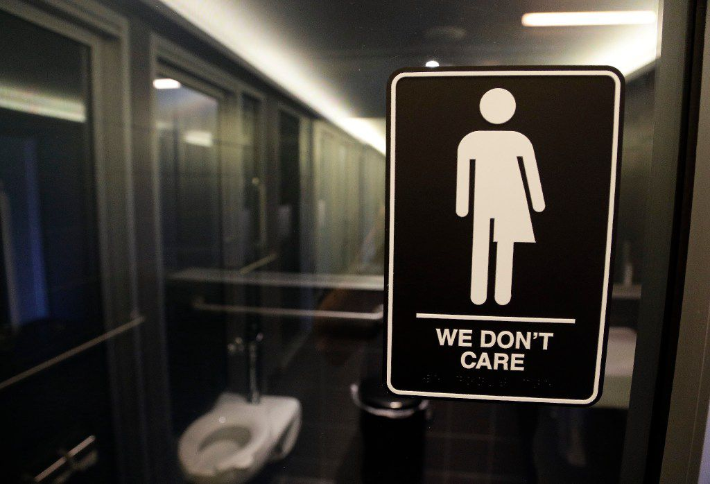 """FILE - This Thursday, May 12, 2016, file photo, shows a sign outside a restroom at 21c Museum Hotel in Durham, N.C. The Associated Press has determined that North Carolina's law limiting LGBT protections will cost the state more than $3 billion in lost business over a dozen years.That's despite Republican assurances that the """"bathroom bill"""" isn't hurting the economy. (AP Photo/Gerry Broome, File)"""