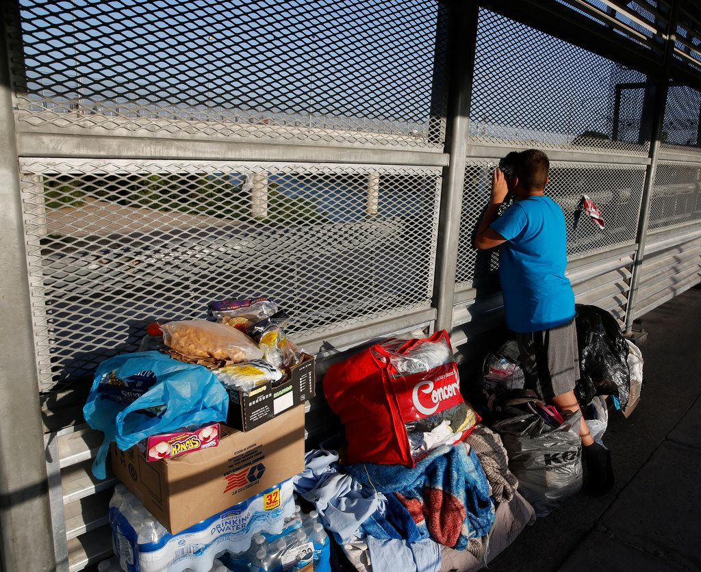 A boy looks at the car bridge over the Rio Grande as he waits on the walking bridge to be processed by U.S. officials on June 9, 2018.