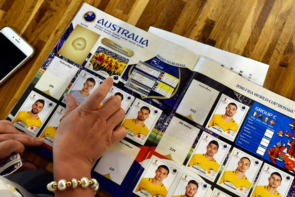 A woman places a sticker of an Australian soccer player on the club sticker page.