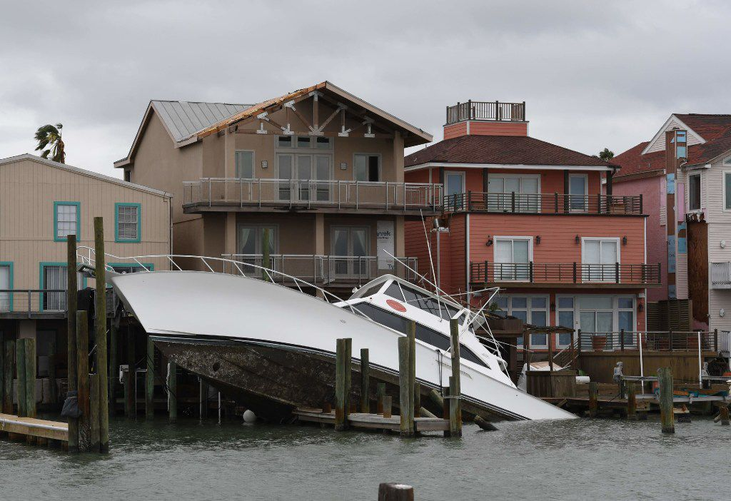 A boat rests partially submerged across boat slips and leaning against the pilings of waterfront residences  Sunday in Port Aransas, Texas, after Hurricane Harvey slammed the Texas coast late Friday.