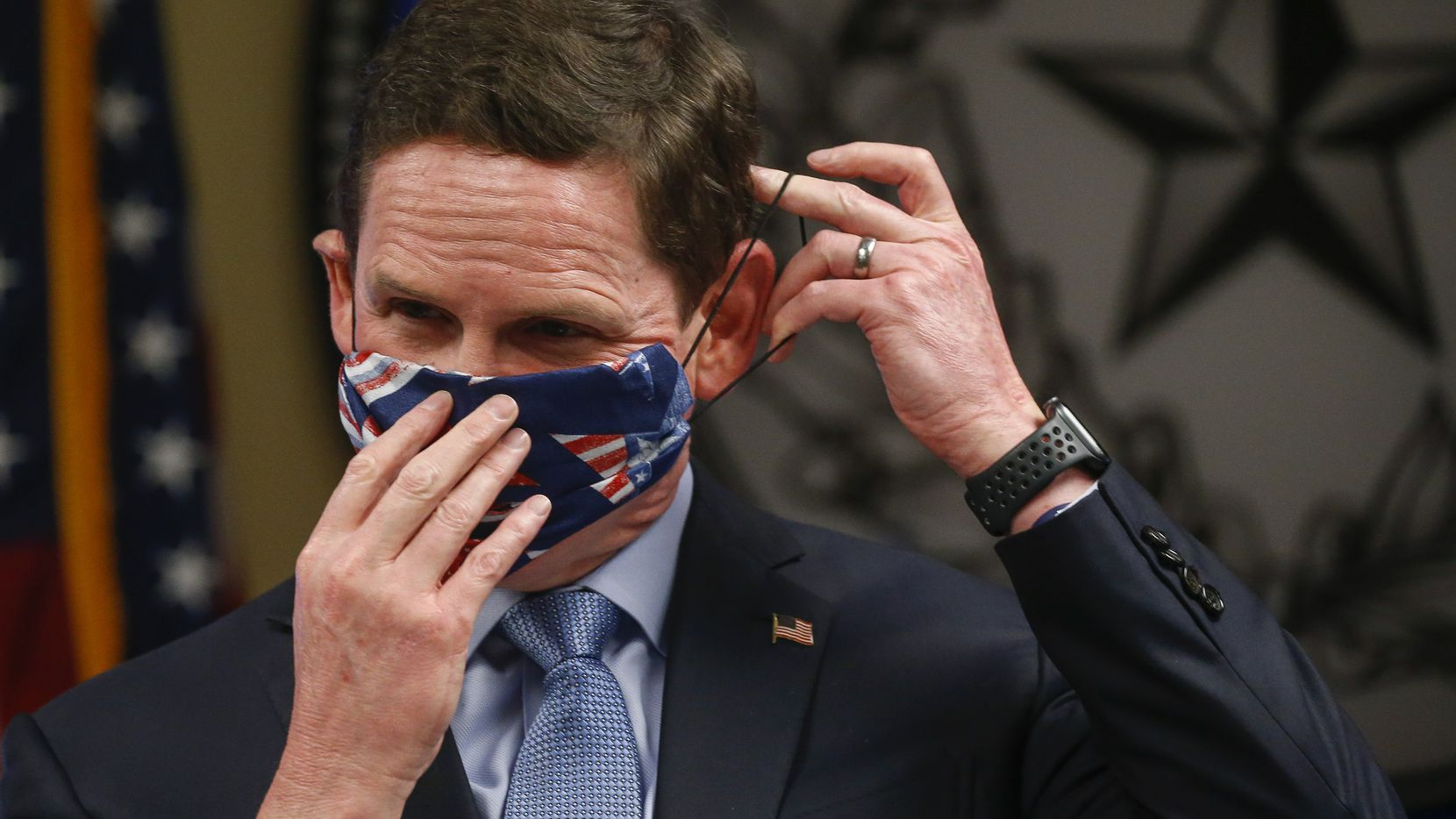 Dallas County Judge Clay Jenkins displays an improvised clothe face mask made with a bandana and hair ties as he addresses members of the media regarding the new coronavirus pandemic on Wednesday, April 8, 2020 at the Dallas County Emergency Operations Center in Dallas.