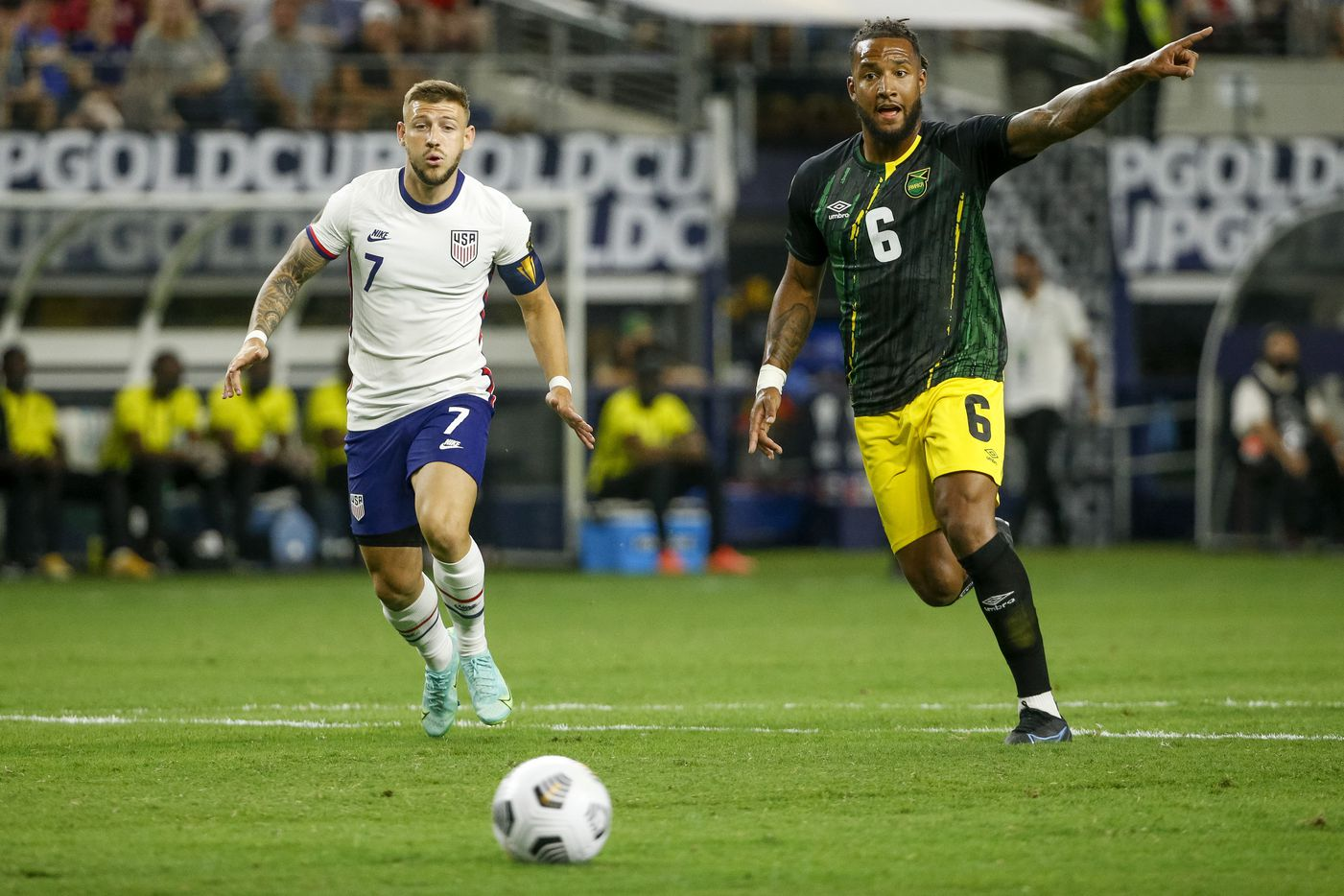 USA forward Paul Arriola (7) and Jamaica defender Liam Moore (6) chase the ball during the first half of a CONCACAF Gold Cup quarterfinal soccer match at AT&T Stadium on Sunday, July 25, 2021, in Arlington. (Elias Valverde II/The Dallas Morning News)