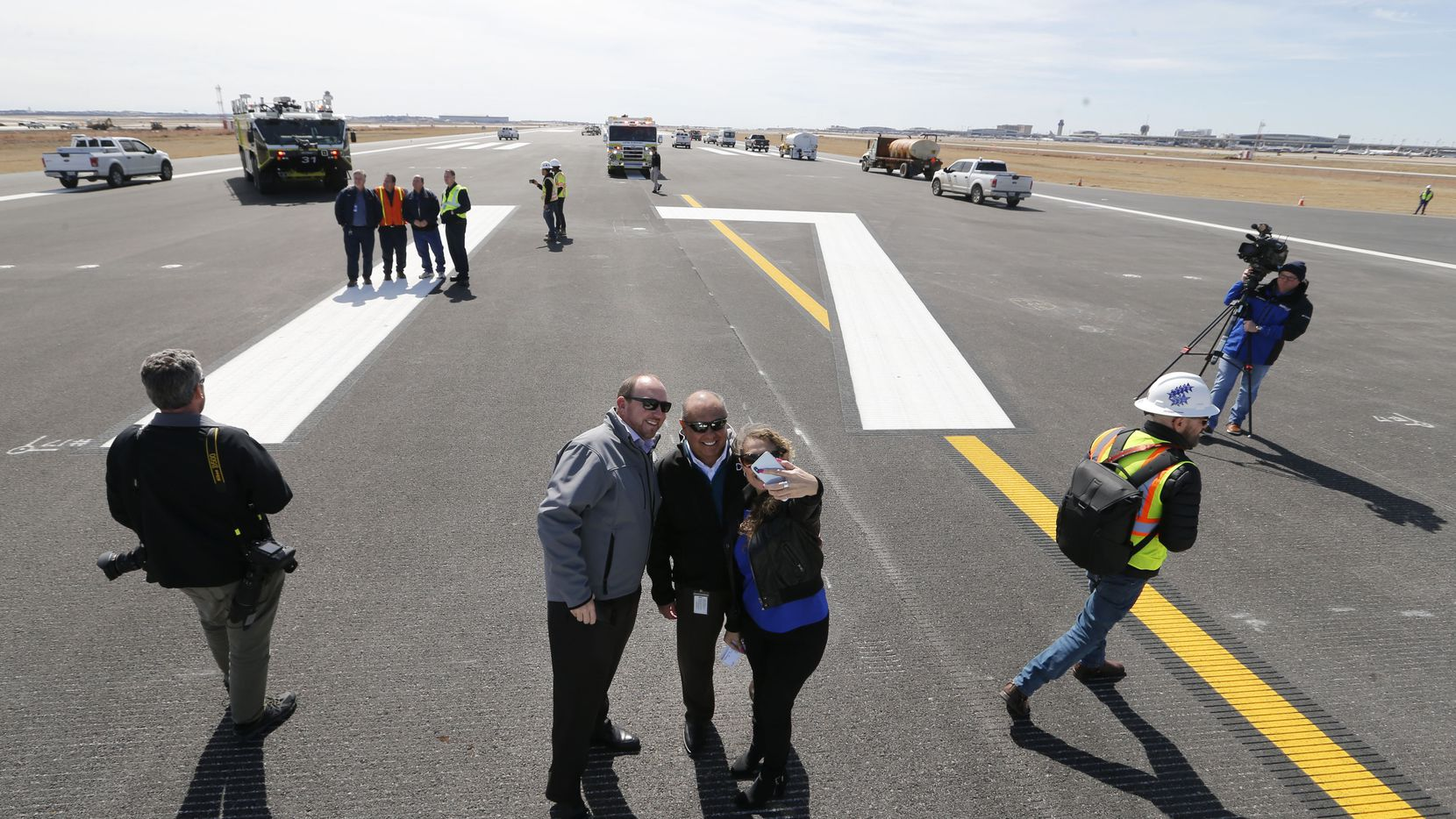 DFW International Airport employees William Grozdanich (group at center, from left), Robert Rodriguez III, and Dana Perez take a group photo together on runway 17C to celebrate the update to it at DFW airport on Monday, February  25, 2019.