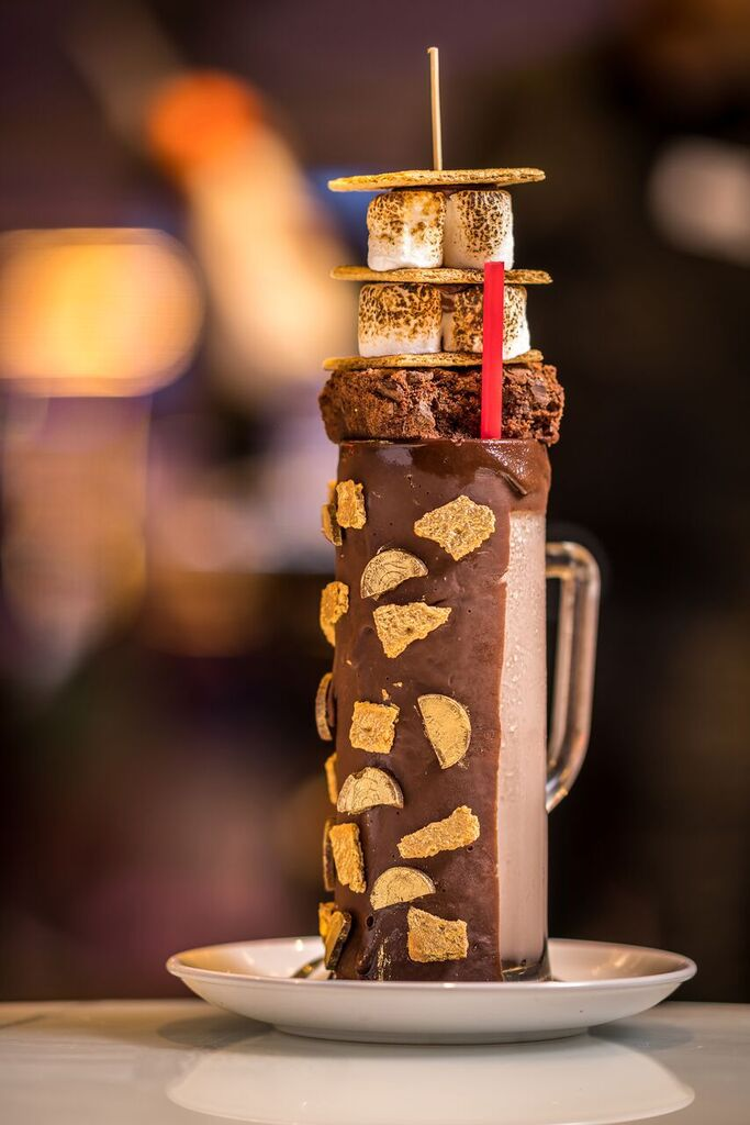 The Campfire Spiked S'mores Milkshake at Sugar Factory costs $31 and is a stacked-high shake spiked with Virginia Black Whiskey. It'll be on the menu when the restaurant and retail store opens in Uptown Dallas in summer 2021.