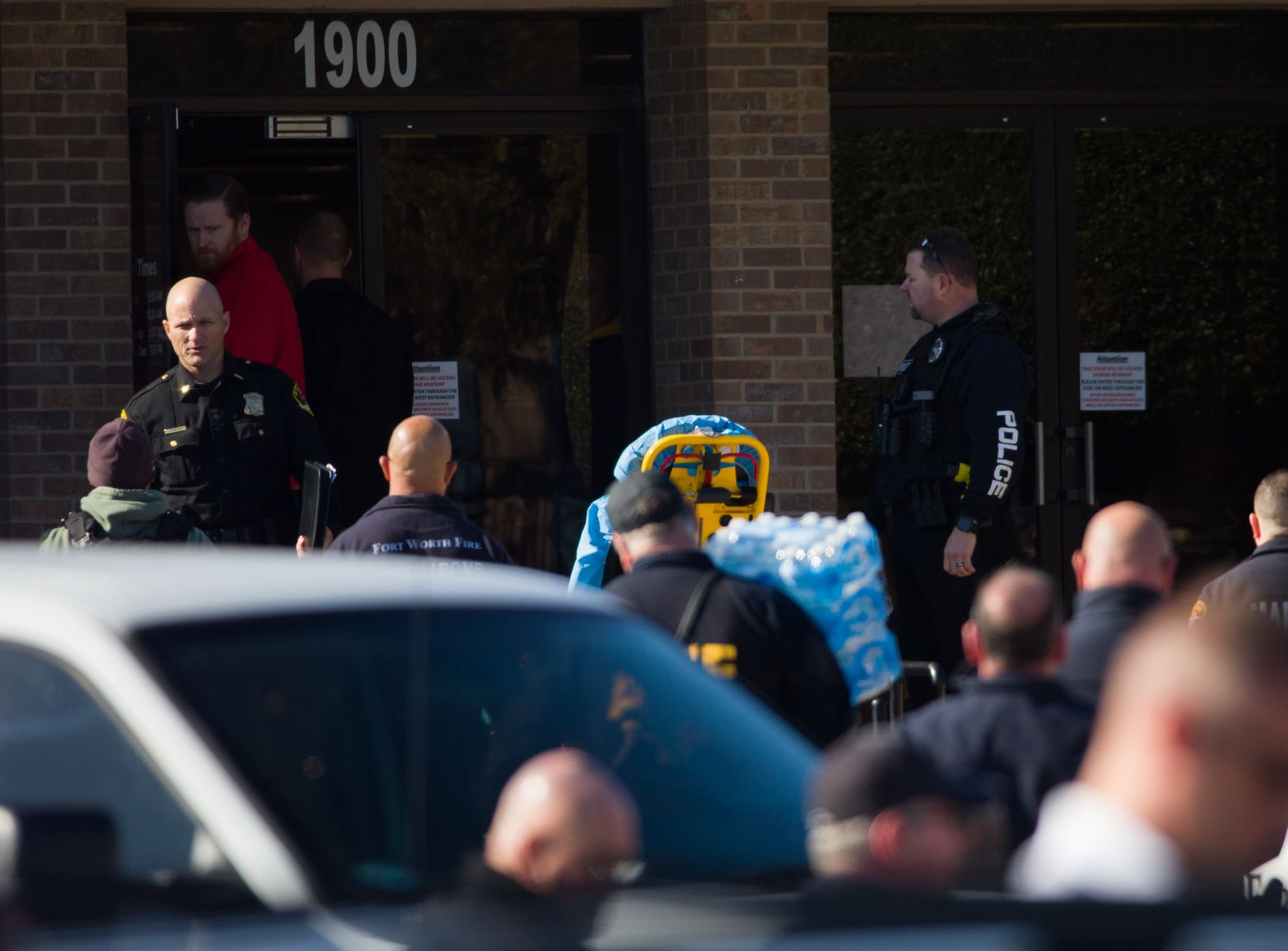 Authorities gather outside the West Freeway Church of Christ, where a gunman opened fire Sunday morning. He fatally shot two people before churchgoers returned fire, killing him, authorities said.