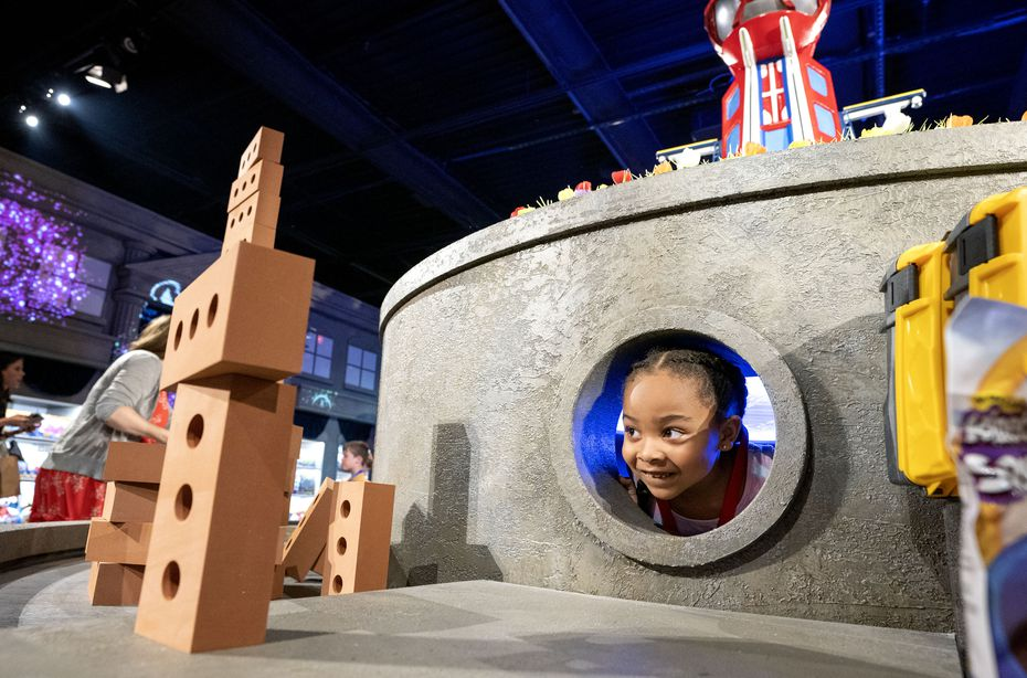 Ariana Brown, 7, peers out of a hole at 'The Paw Patrol Experience' in Dallas.