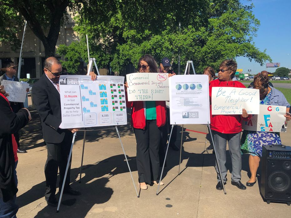 """Representatives of Communities United for a Greater Dallas hold signs with messages saying """"Be a good neighbor"""" and """"Do the right thing!"""" before a news conference Monday, April 15, 2019."""