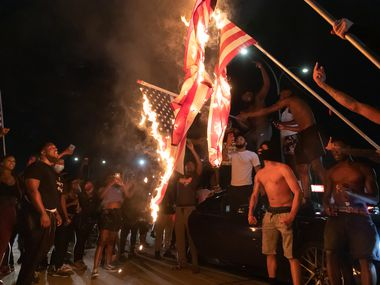 Protesters cheer as American flags burn outside the Ott Cribbs Public Safety Center during a demonstration against police brutality June 1, 2020, in Arlington. Protesters threw the flag poles at the police station after the flags had burned.