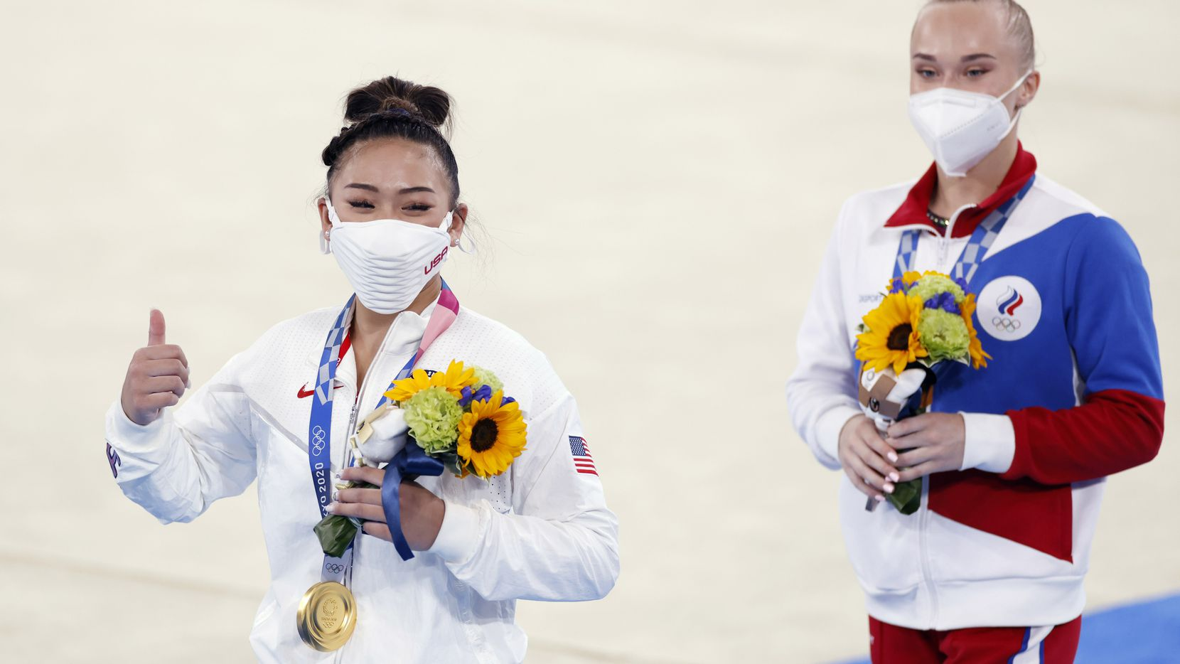 Gold medal winner USA's Sunisa Lee, and bronze medal winner ROC's Angelina Melnikova walk the stage after receiving their medals in the women's all-around final at the postponed 2020 Tokyo Olympics at Ariake Gymnastics Centre, on Thursday, July 29, 2021, in Tokyo, Japan. (Vernon Bryant/The Dallas Morning News)