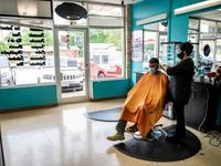 A young man gets his hair cut at a barbershop amid the coronavirus pandemic in Austin, Texas on May 8, 2020 following a slow reopening of the Texas economy.