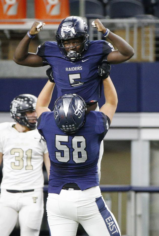 Wylie East's Eno Benjamin (5) celebrates a touchdown with Sean Addicks lifting him against  The Colony during their high school playoff football game at AT&T Stadium in Arlington, Texas November 13, 2015.   (Nathan Hunsinger The Dallas Morning News)