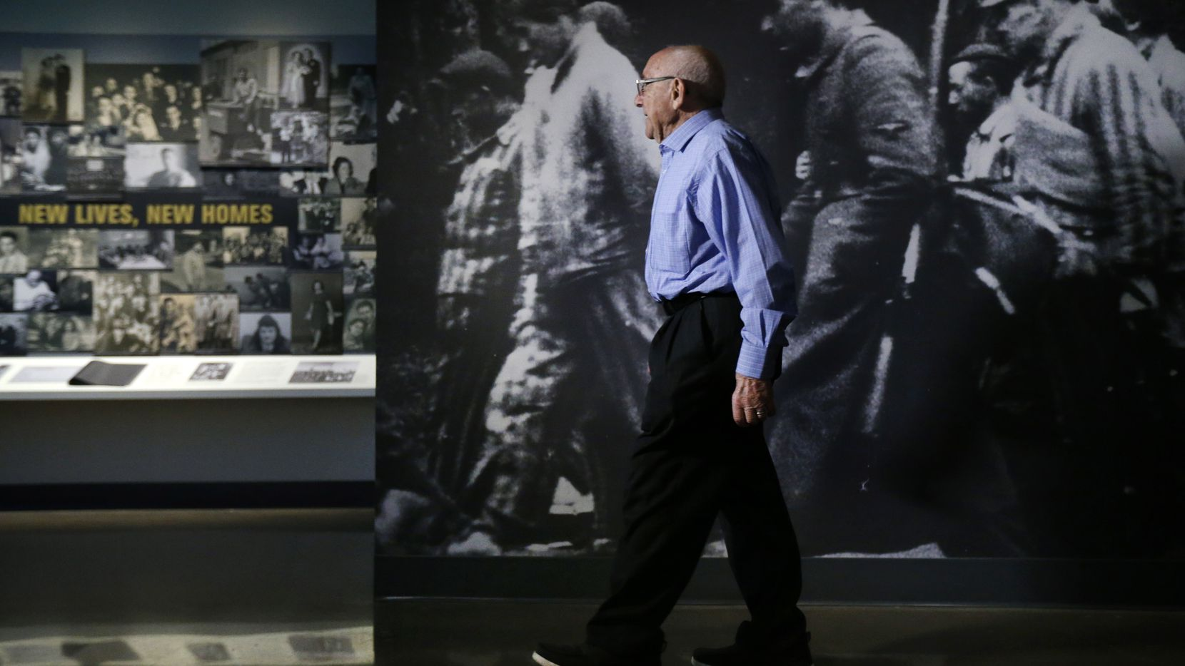 Holocaust survivor Max Glauben walks past a life-sized photo of prisoners on a death march from Dachau, Germany, as he toured the new Dallas Holocaust and Human Rights Museum in downtown Dallas.