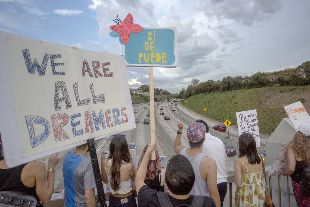 LOS ANGELES, CA - SEPTEMBER 10: People hold signs over the 110 freeway as thousands of immigrants and supporters join the Defend DACA March to oppose the President Trump order to end DACA on September 10, 2017 in Los Angeles, California. The Obama-era Deferred Action for Childhood Arrivals program provides undocumented people who arrived to the US as children temporary legal immigration status for protection from deportation to a country many have not known, and a work permit for a renewable two-year period. The order exposes about 800,000 so-called Ã'dreamersÓ who signed up for DACA to deportation. About a quarter of them live in California. Congress has the option to replace the policy with legislation before DACA expires on March 5, 2018.  (Photo by David McNew/Getty Images)