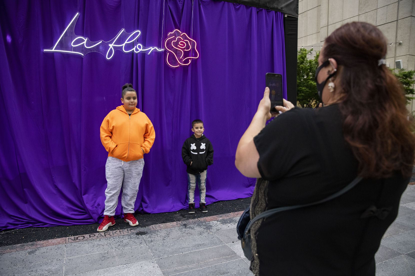 """Antonio (left), 11, poses with brother Lionel, 6, as mom Berdha Reyna takes a photo of them during the Selena 50th birthday celebration at Jaxon Beer Garden on Friday, April 16, 2021. Reyna said that her kids always sing Selena's songs when they pass the mural on West Jefferson Blvd. """"Su musica es una herencia, Reyna said. Meaning, Selena's music is like an inheritance."""