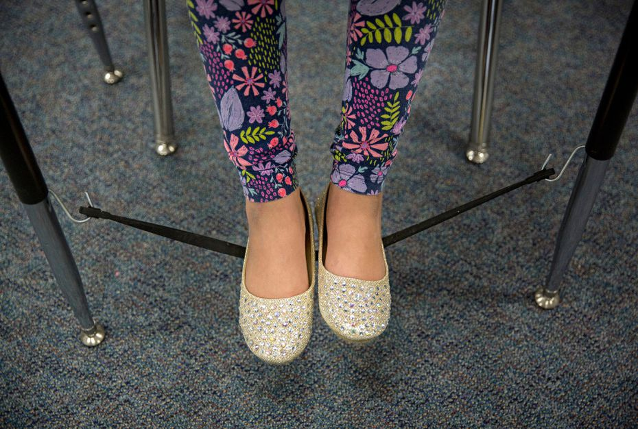 """Crystal Ruiz balances her feet on a """"wiggle string"""" attached to her desk at Davis Elementary Monday, September 19, 2016 in Carrollton, Texas."""