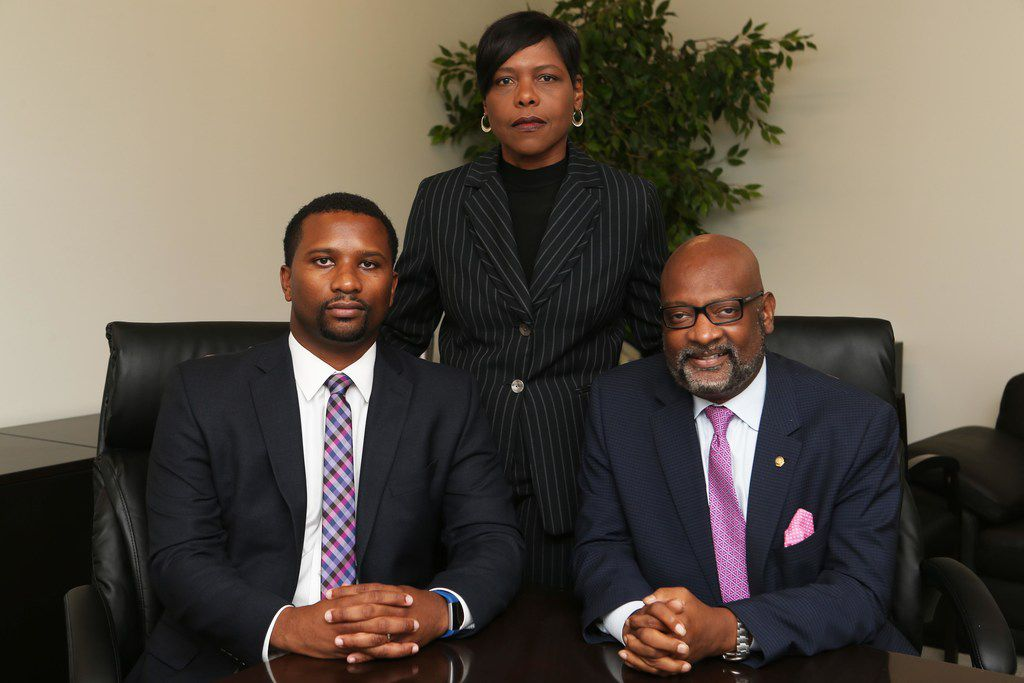 From left: Attorney Keron Wright, Delsa Thomas, the defendant, and attorney Aaron Wiley pose for a photograph at Wiley's office in Dallas on July 26, 2018.