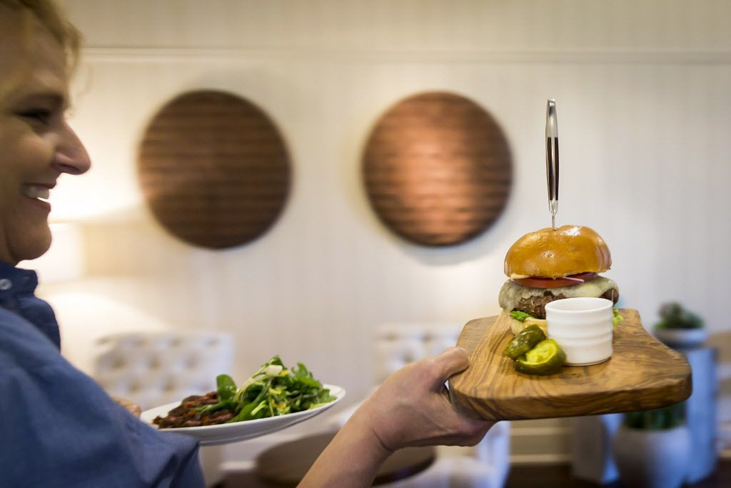 Server Whitney Woods carries the Akaushi Beef Burger into the dining area at LAW at the Four Seasons Resort and Club Dallas at Las Colinas on Wednesday, March 30, 2016, in Irving. (Smiley N. Pool/The Dallas Morning News)