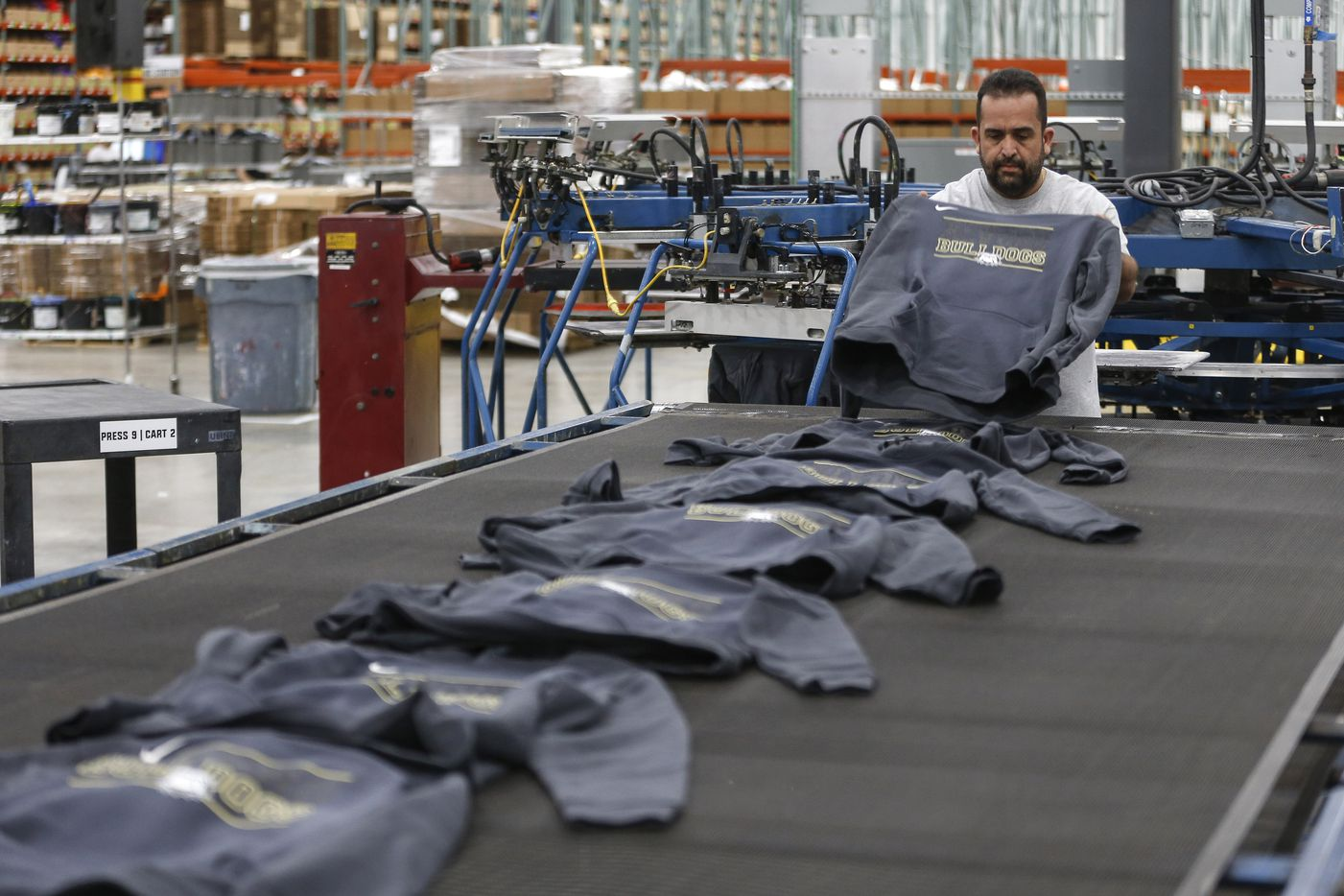 Workers work on custom design apparel orders at BSN Sports on Thursday.
