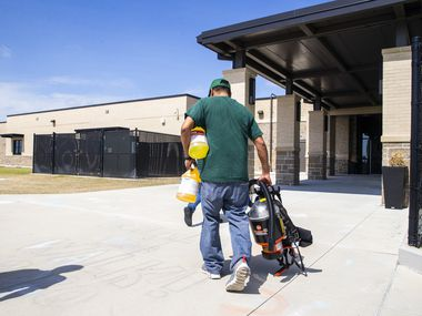Custodian George Cox (right) carries a respirator and cleaning supplies into Jim Spradley Elementary School in Frisco, Texas, on Thursday, March 12, 2020.