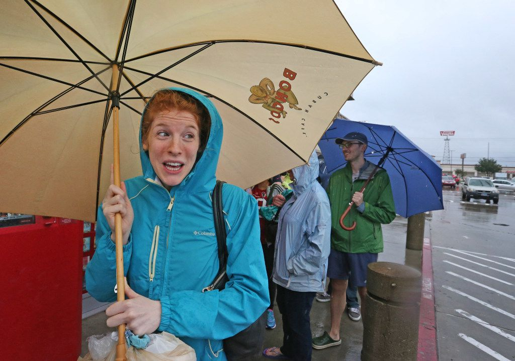 Former Plano resident Margaret Evans stands in line with other shoppers outside in the rain to get into the Kroger's store at North Shepherd and 11th Street in Houston.