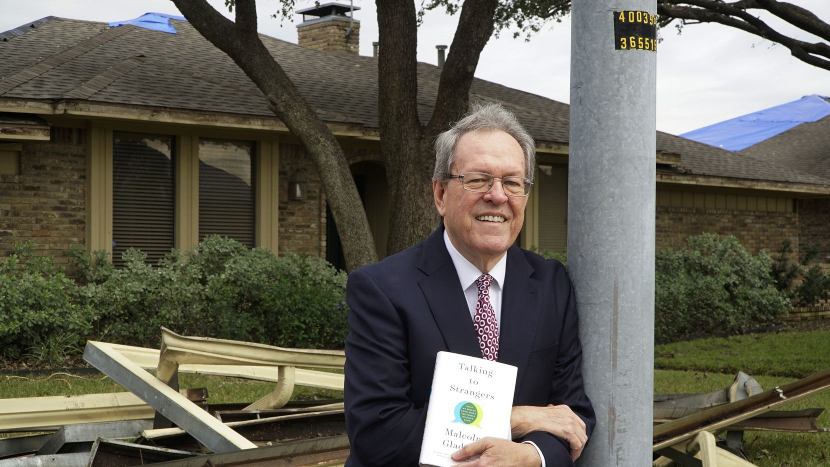 "Randy Mayeux poses with Malcolm Gladwell's book ""Talking to Strangers"" at his home in Richardson. Mayeux's home was damaged during a tornado, and the book helped him decide which company to hire,"