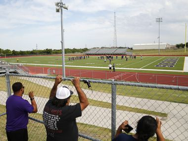 Parents of players Aaron Clark (left), Jose Chairez (center) and Corina Chairez (far right) watch practice from the gate during the first day of high school football practice for 4A's Farmersville High School in Farmersville, Texas on Monday, August 3, 2020. (Vernon Bryant/The Dallas Morning News)