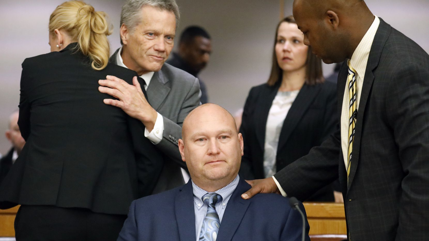 Former Dallas police officer Christopher Hess (seated) takes a moment for himself as his attorneys congratulate one another after Hess was found not guilty of aggravated assault.