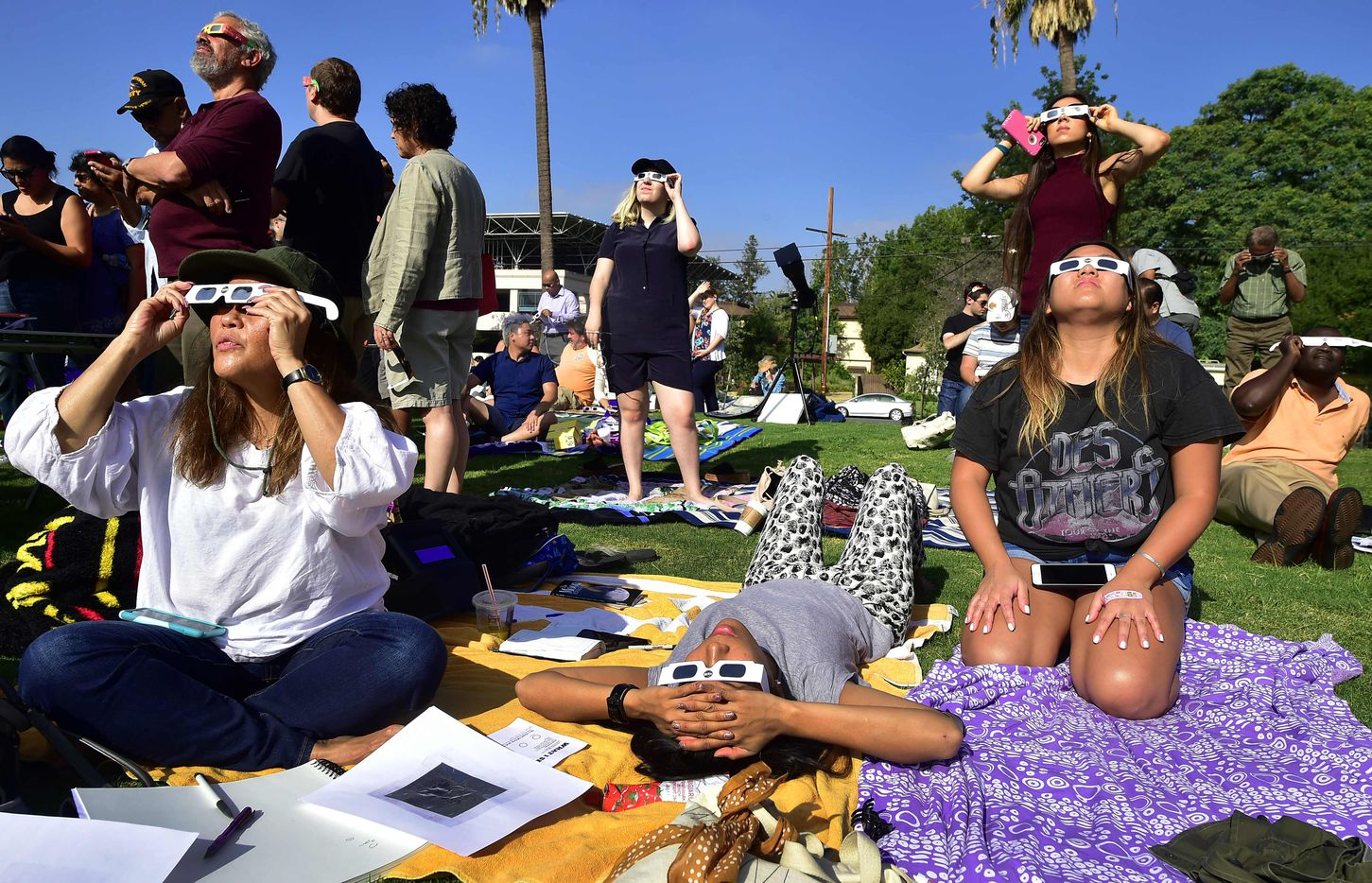 People use solar eclipse glasses to view the solar eclipse from Beckman Lawn at Caltech in Pasadena, Calif. Emotional sky-gazers on the West Coast cheered and applauded.
