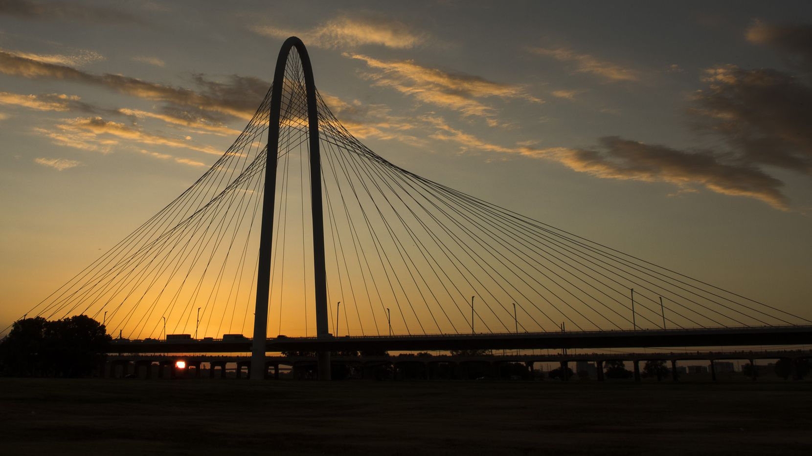 The sun sets behind the Margaret Hunt Hill Bridge in Dallas.