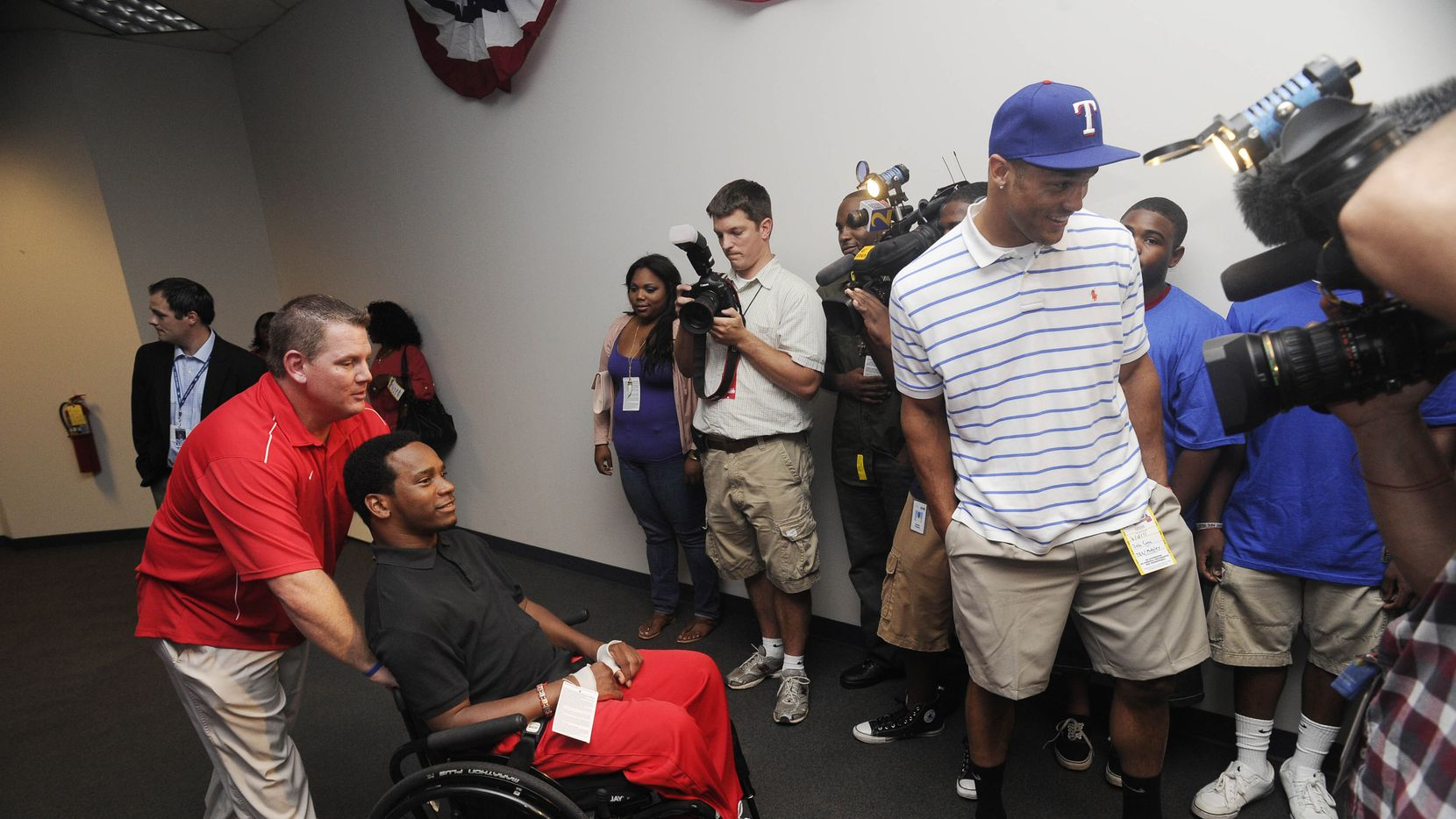 Recent Texas Ranger draftee, Johnathan Taylor, who sustained partial paralysis in an outfield collision with Georgia teammate and fellow draftee Zach Cone, follows behind Cone while being pushed by Rangers scout Ryan Coe as they arrive for a press conference introducing the team's draft selections, before their baseball game against the Atlanta Braves, Saturday, June 18, 2011.
