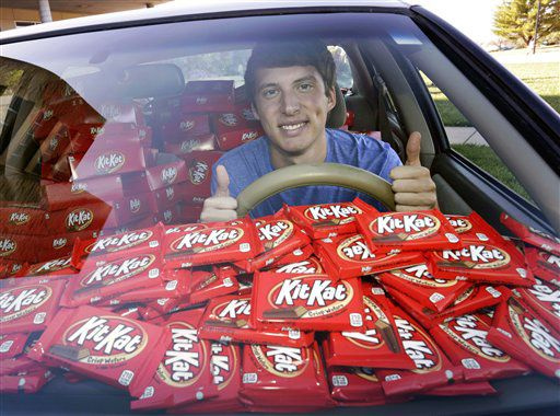 estudiante de la Universidad Kansas State, mientras posa en su automóvil con casi 6.500 barras de chocolate Kit Kat en Manhattan, Kansas./AP